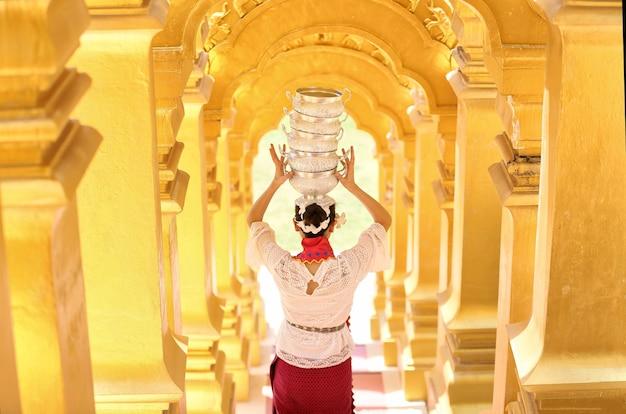 Jeune fille avec un bol de riz traditionnel birman sur la main à la belle pagode d'or au myanmar