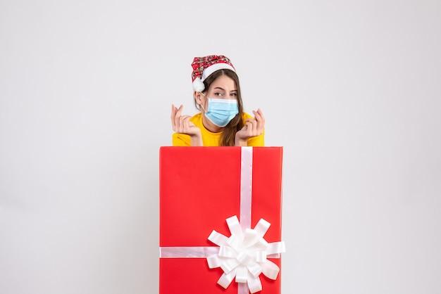 Jeune fille avec bonnet de noel et masque debout derrière gros cadeau de noël sur blanc