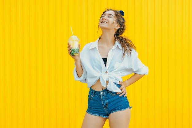 Jeune fille bouclée heureuse tenant un cocktail sans alcool sur un mur jaune