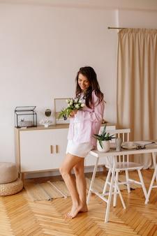 Jeune fille avec un bouquet de fleurs au bureau à domicile