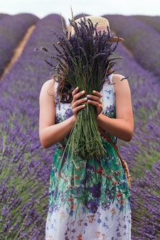 Une jeune fille avec un bouquet de lavande se dresse au milieu d'un champ de lavande