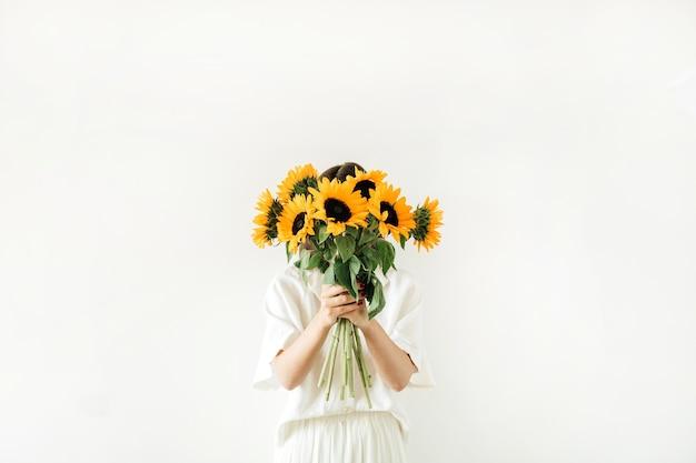 Jeune fille avec bouquet de tournesols en mains sur blanc