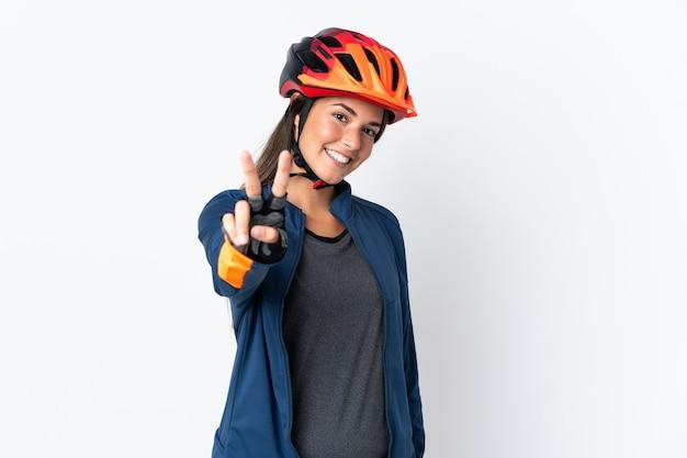 Jeune fille brésilienne cycliste isolée sur mur blanc souriant et montrant le signe de la victoire