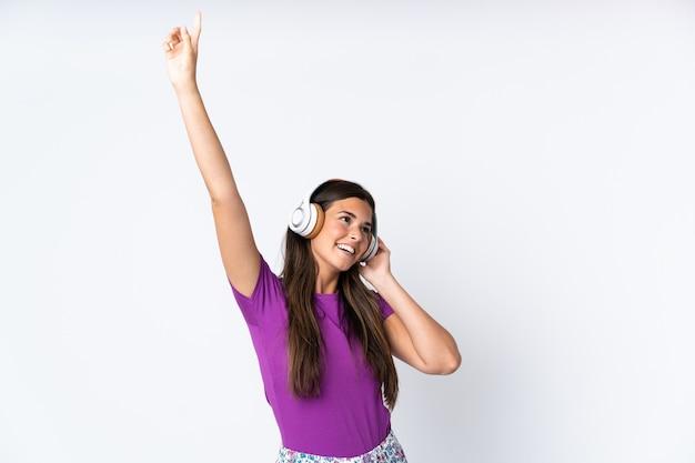 Jeune fille brésilienne isolée sur fond blanc en pyjama et tenant un oreiller et écouter de la musique