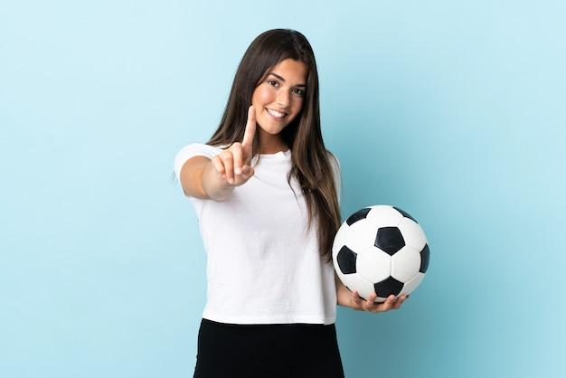 Jeune fille brésilienne de joueur de football isolé sur fond bleu montrant et soulevant un doigt