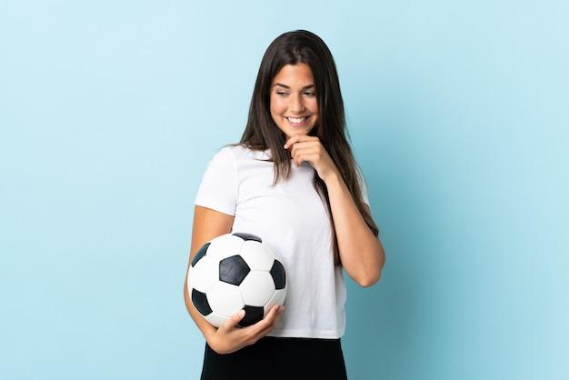 Jeune fille brésilienne de joueur de football isolé sur fond bleu à la recherche sur le côté et souriant