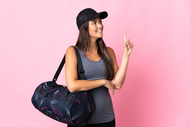 Jeune fille brésilienne de sport avec sac de sport isolé sur un mur rose pointant vers le haut une excellente idée