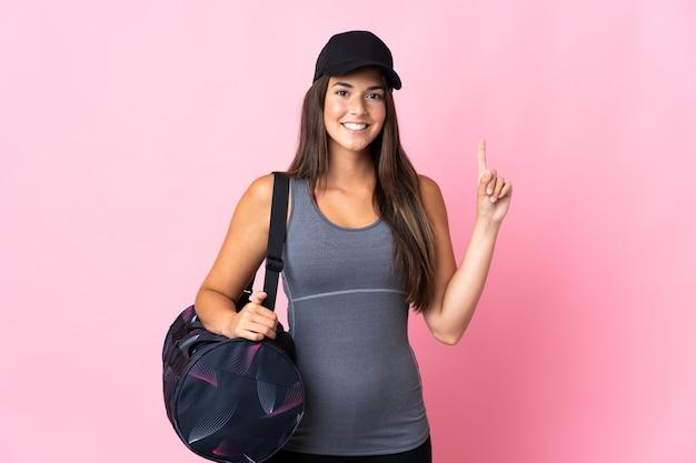 Jeune fille brésilienne de sport avec sac de sport sur rose pointant vers le haut une excellente idée
