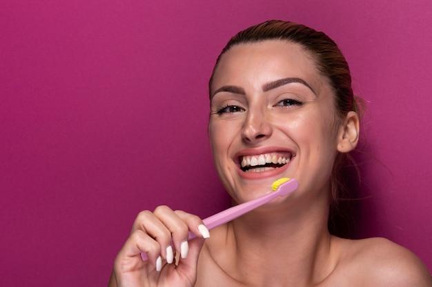 Jeune fille avec une brosse à dents en riant