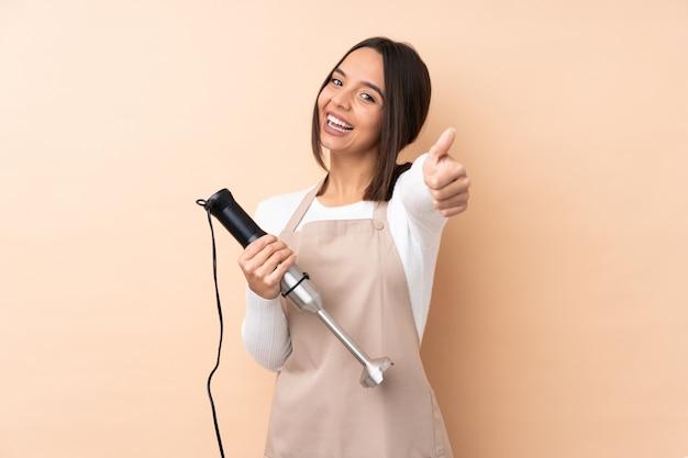 Jeune fille brune à l'aide d'un mélangeur à main sur un mur isolé avec les pouces vers le haut parce que quelque chose de bien s'est produit