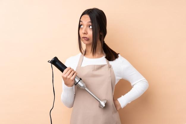 Jeune fille brune à l'aide d'un mixeur à main sur un mur isolé avec l'expression du visage confus