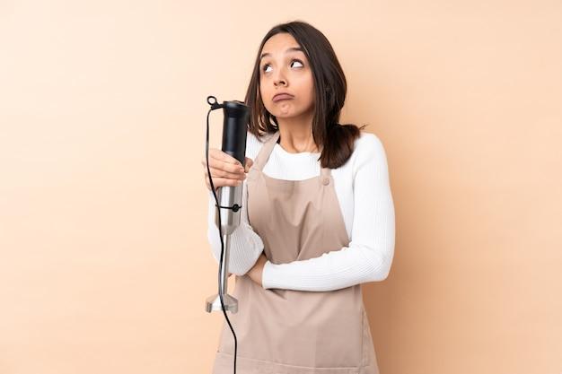 Jeune fille brune à l'aide d'un mixeur à main sur un mur isolé faisant le geste de doutes tout en soulevant les épaules