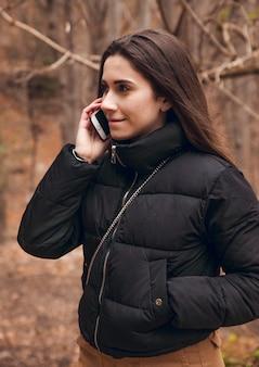 Jeune fille brune appelant par téléphone en forêt