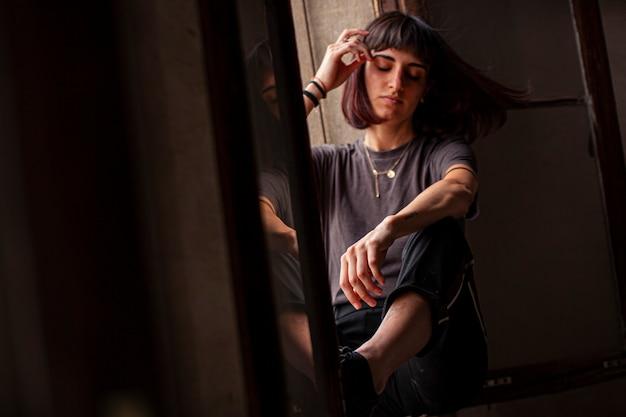 Jeune fille brune assise sur une fenêtre d'une maison ancienne et abandonnée
