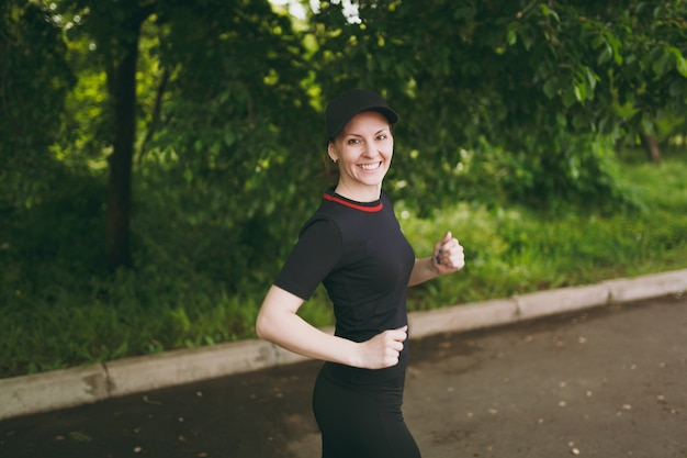 Jeune fille brune athlétique souriante en uniforme noir et entraînement de casquette faisant des exercices de sport, courant et regardant la caméra sur le chemin dans le parc de la ville à l'extérieur