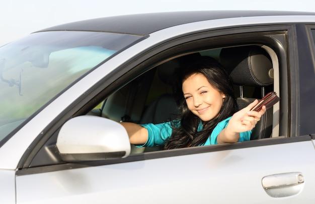 Jeune fille brune au volant de la conduite affiche des documents