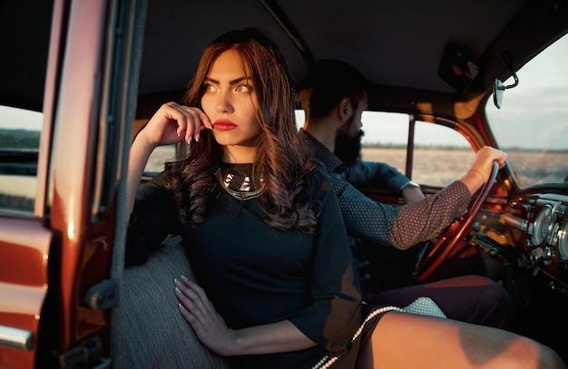Jeune fille brune aux cheveux longs dans une robe noire élégante est assise dans une voiture rétro avec un homme brutal barbu au volant. couple marié en querelle