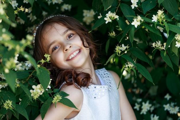 Jeune fille brune aux cheveux longs noirs sur fond de feuillage et de fleurs dans le parc. portrait d'enfant. photo de haute qualité