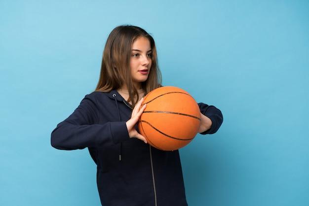 Jeune fille brune sur bleu isolé avec ballon de basket