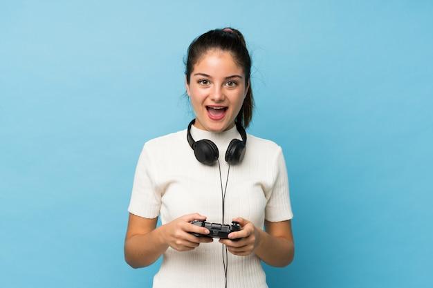 Jeune fille brune sur bleu isolé jouant aux jeux vidéo