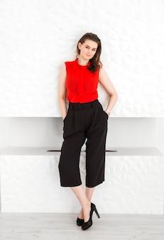 Jeune fille brune dans un chemisier rouge, un pantalon capri noir et des chaussures à talons hauts posant sur le fond d'une cheminée blanche.