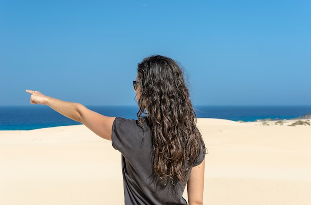 Jeune fille brune dans la dune pointant vers la mer.
