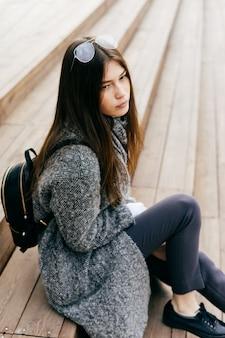 Jeune fille brune dans un manteau gris à la mode est assise sur les marches à l'extérieur, style de rue