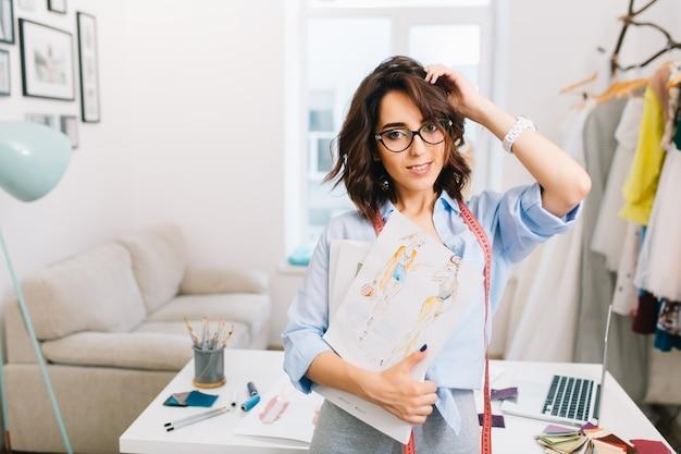 Une jeune fille brune dans une robe grise et une chemise bleue se tient près de la table dans un atelier de studio. elle tient des croquis dans ses mains. elle regarde la caméra.