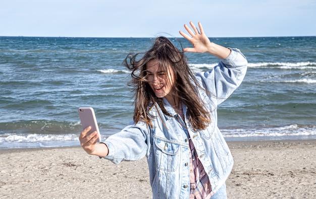 Jeune fille brune dans une veste en jean fait une photo sur la caméra du téléphone. concept de voyage et de nouvelles expériences.