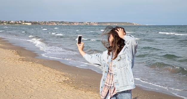 Jeune fille brune dans une veste en jean fait une photo sur un téléphone appareil photo selfie dans le contexte de la mer. concept de voyage et de nouvelles expériences.