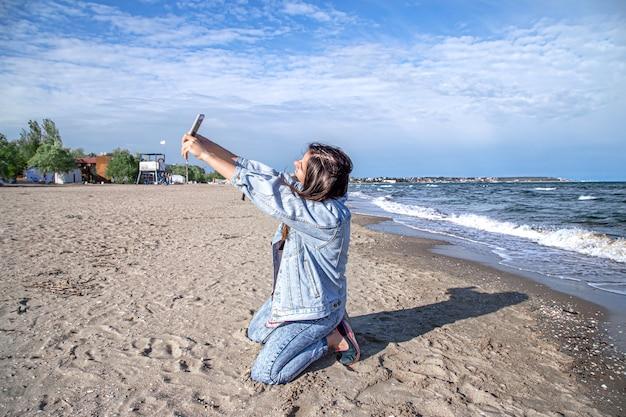 Jeune fille brune dans une veste en jean prend une photo sur l'appareil photo du téléphone. le concept de voyage et de nouvelles expériences.