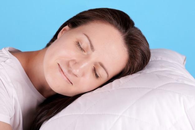 Jeune fille brune dormir sur un oreiller blanc, les yeux fermés. isolé sur fond bleu.
