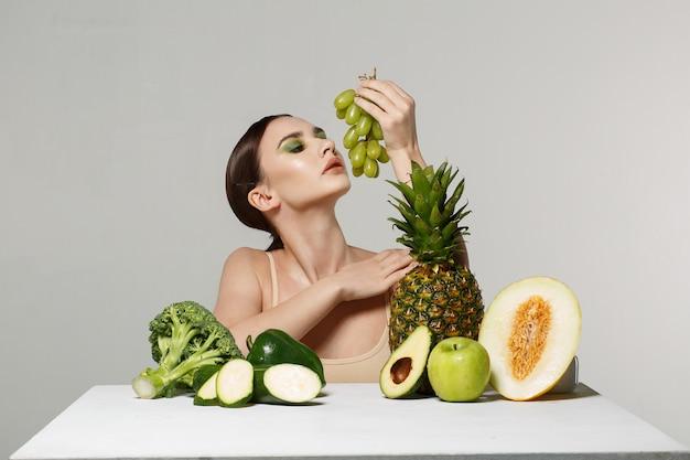 Jeune fille brune avec du maquillage posant avec des fruits