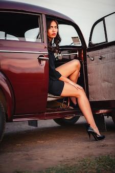Jeune fille brune élancée dans une robe noire est assise dans une voiture rétro marron et a exposé une belle jambe dans des chaussures à talons hauts