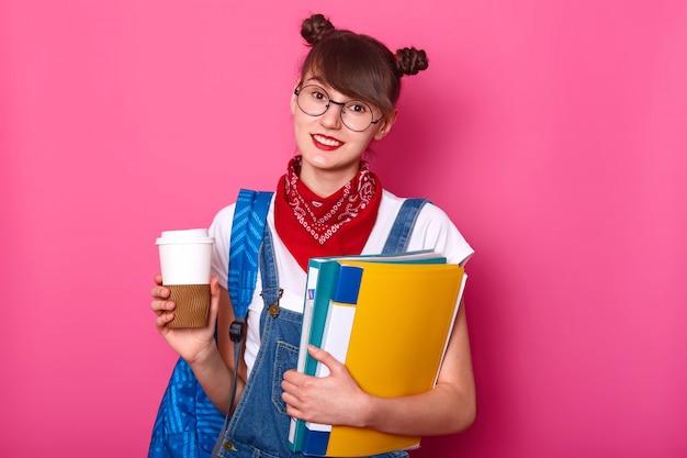 Jeune fille brune élancée en t-shirt décontracté blanc, salopette et bandana sur le cou, tenant une tasse de café et un dossier avec des documents, posant isolé sur rose. concept de jeune.