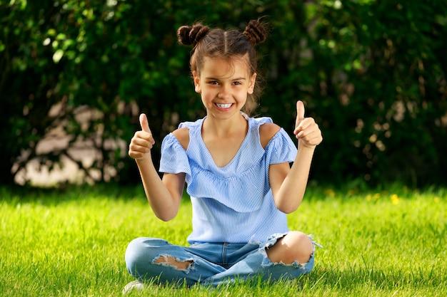 Jeune fille brune est assise sur l'herbe dans le parc et montre ses pouces. photo de haute qualité