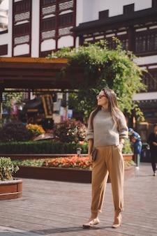 Jeune fille brune explorant une place locale à shanghai en chine