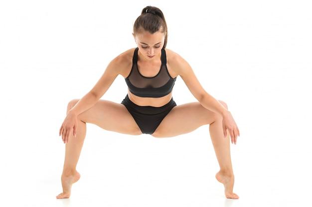 Jeune fille brune, faire du yoga dans un maillot de bain noir