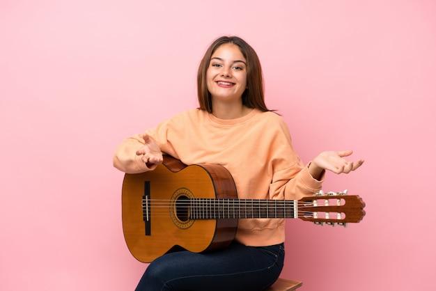 Jeune fille brune avec fond de guitare avec une expression faciale choquée