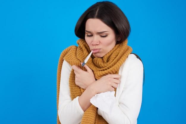 Jeune fille brune a froid prenant la température