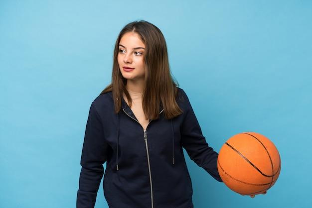 Jeune fille brune sur isolé avec ballon de basket