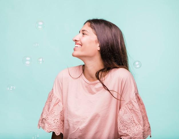 Jeune fille brune jouant avec des bulles de savon