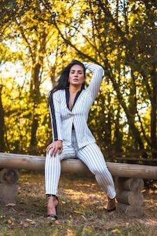 Jeune fille brune latine dans un costume blanc très élégant avec des rayures noires. mode posée dans un beau parc assis