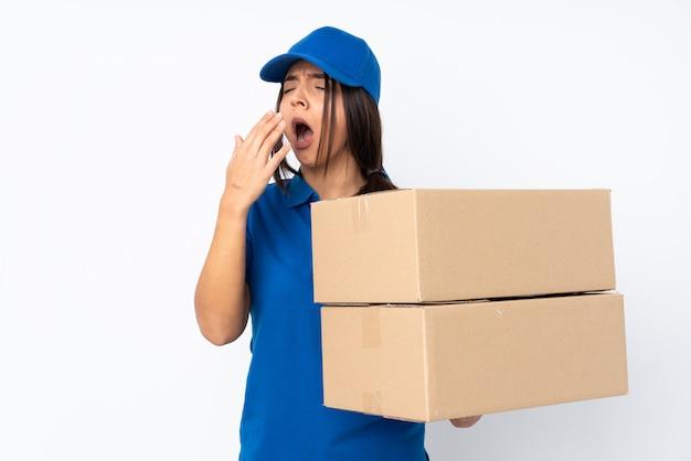 Jeune fille brune de livraison sur bâillement blanc et couvrant la bouche grande ouverte avec la main