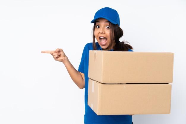 Jeune fille brune de livraison sur blanc surpris et pointant le côté