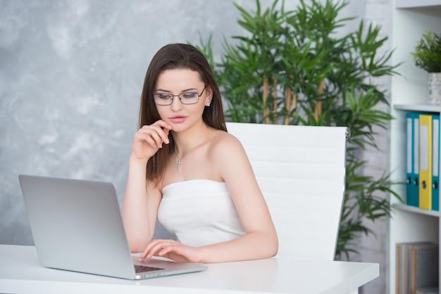 Une jeune fille brune avec des lunettes dans une robe blanche est assise dans le bureau à la table. la femme travaille à l'ordinateur portable. basse vision ou accessoire de mode.