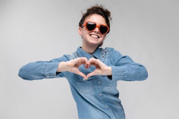 Jeune fille brune avec des lunettes en forme de coeur.