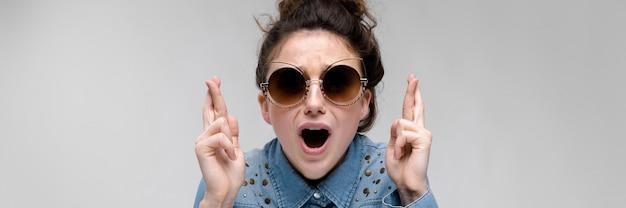 Jeune fille brune à lunettes noires. lunettes de chat. les cheveux sont rassemblés en un chignon. la fille a croisé ses doigts.