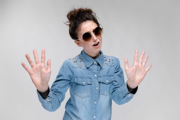 Jeune fille brune à lunettes noires. lunettes de chat. les cheveux sont rassemblés en un chignon. la fille montre ses mains.