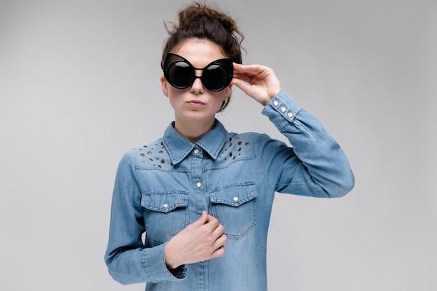 Jeune fille brune à lunettes noires.